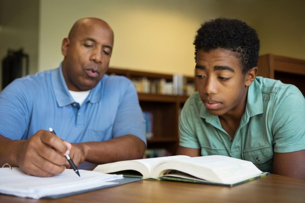 Portrait of teacher assisting a teenage student with homework in